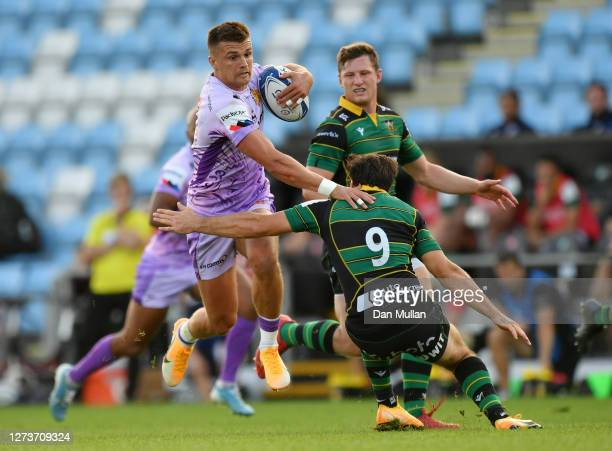 Henry Slade of Exeter Chiefs makes a break past Henry Taylor of Northampton Saints during the Heineken Champions Cup Quarter Final match between...