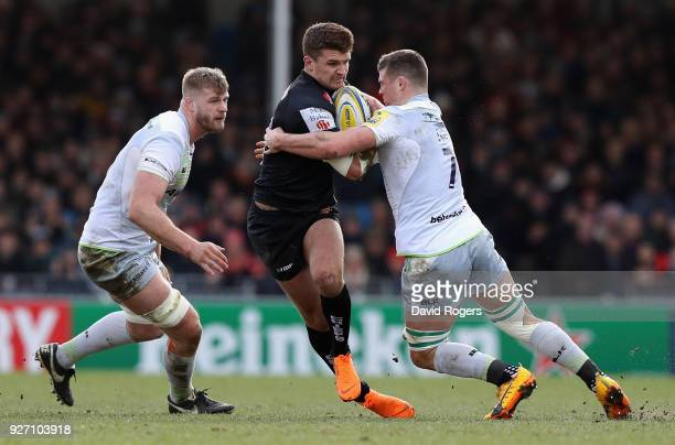Henry Slade of Exeter is tackled by Ben Earl as George Kruis looks on during the Aviva Premiership match between Exeter Chiefs and Saracens at Sandy...