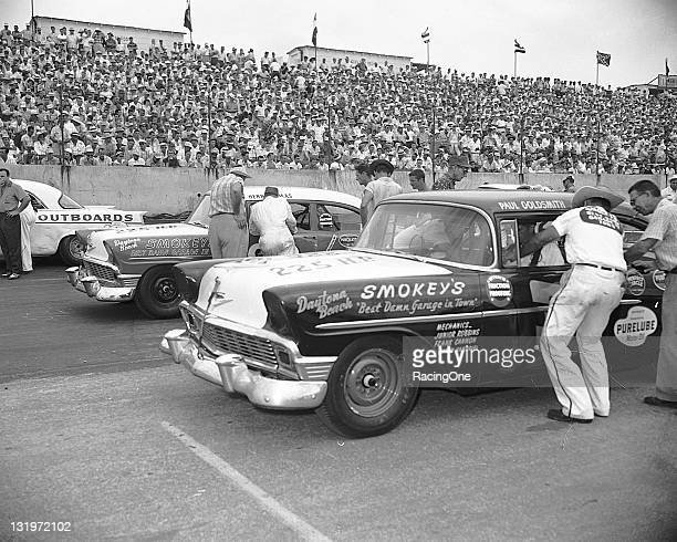 """Henry """"Smokey"""" Yunick helps buckle his driver Paul Goldsmith into his Chevrolet prior to the start of the Southern 500 NASCAR Cup race at Darlington..."""
