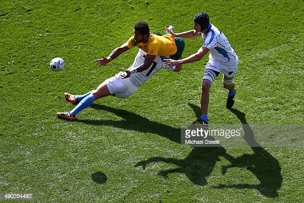 Henry Speight of Australia passes the ball as he is tackled by Rodrigo Silva and Matias Beer of Uruguay during the 2015 Rugby World Cup Pool A match...