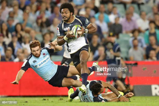 Henry Speight of the Brumbies evades the defence of Andrew Kellaway and Israel Folau of the Waratahs in his way to scoring a try during the round...