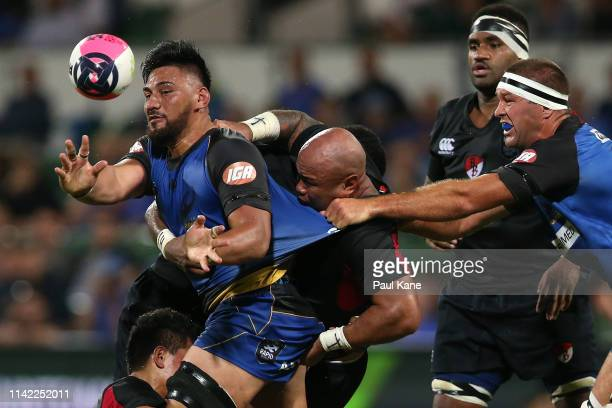 Henry Stowers of the Force offloads the ball while being tackled by Kali Hala and Nili Latu of the Dragons during the Rapid Rugby match between the...