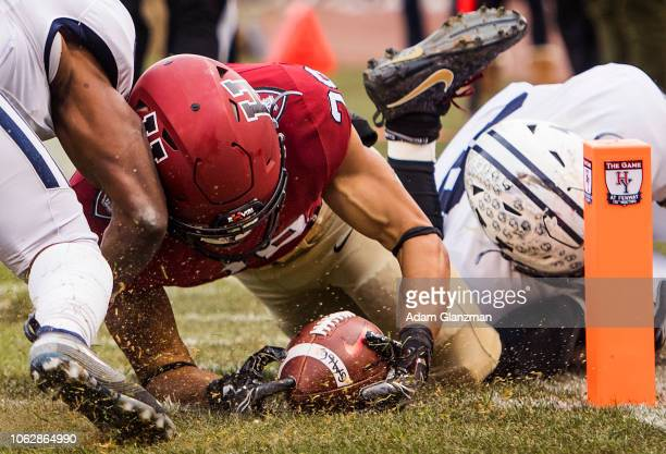 Henry Taylor of the Harvard Crimson scores a touchdown while being tackled by Noah Pope of the Yale Bulldogs in the second quarter of a game at...