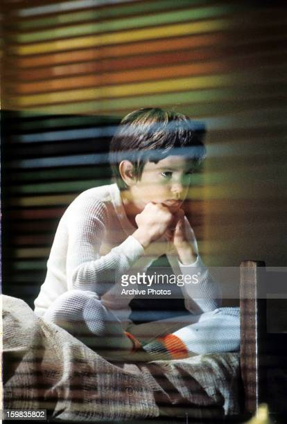 Henry Thomas pondering in his room in a scene from the film 'ET The ExtraTerrestrial' 1982