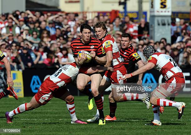 Henry Trinder and Andy Hazell of Gloucester tackle Joel Tomkins of Saracens during the Aviva Premiership match between Gloucester and Saracens at...
