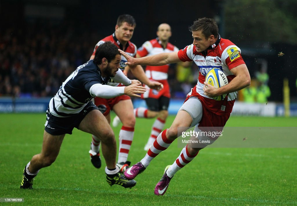 Henry Trinder of Gloucester beats the tackle of Scott Mathie of Sale to score a try during the AVIVA Premiership match between Sale Sharks and Gloucester at Edgeley Park on October 8, 2011 in Stockport, England.