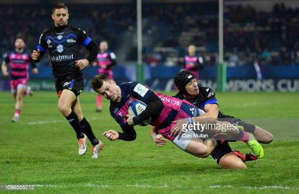 Henry Trinder of Gloucester goes over to score his side's first try as he is tackled by Armand Batlle of Castres Olympique during the Champions Cup...
