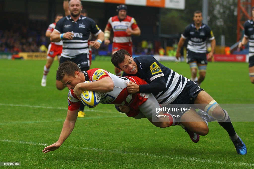 Henry Trinder of Gloucester holds off Rob Miller of Sale to score a try during the AVIVA Premiership match between Sale Sharks and Gloucester at Edgeley Park on October 8, 2011 in Stockport, England.