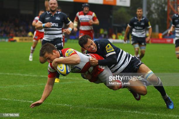 Henry Trinder of Gloucester holds off Rob Miller of Sale to score a try during the AVIVA Premiership match between Sale Sharks and Gloucester at...