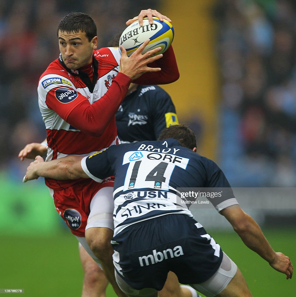 Henry Trinder of Gloucester is tackled by Tom Brady of Sale during the AVIVA Premiership match between Sale Sharks and Gloucester at Edgeley Park on October 8, 2011 in Stockport, England.