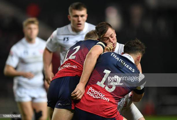 Henry Trinder of Gloucester Rugby is tackled by Sam Bedlow of Bristol and Piers O'Conor of Bristol during the Premiership Rugby Cup match between...