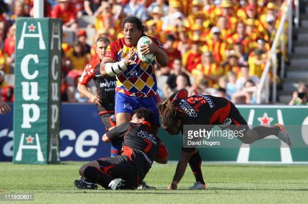 Henry Tuilagi of Perpigan is tackled by George Smith during the Heineken Cup quarter final match between Perpignan and Toulon at the Olympic Stadium...