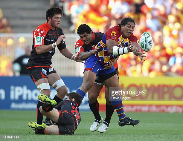 Henry Tuilagi of Perpigan passes the ball as he is tackled during the Heineken Cup quarter final match between Perpignan and Toulon at the Olympic...