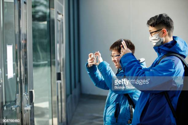 Henry Wang left and Zhao Ruzhang of Beijing China take pictures outside the John F Kennedy Presidential Library in the Dorchester neighborhood of...
