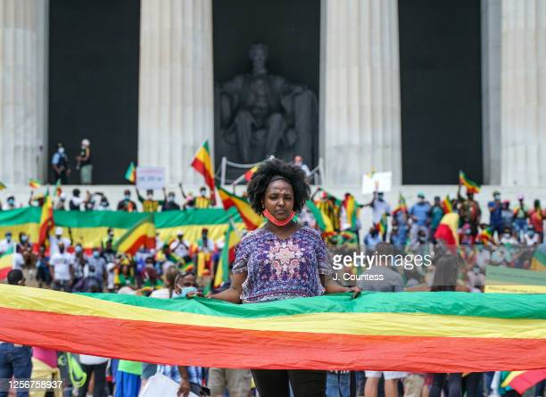 Henu Hileu holds a portion of the Ethiopian flag as she and other members of the Ethiopian community representing multiple ethnic groups gather on...