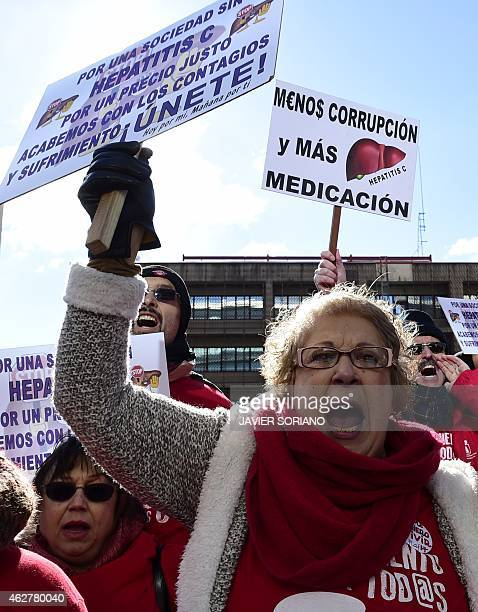 Hepatitis C sufferers and supporters hold placards during a demonstration outside of US laboratory Gilead Sciences office in Madrid on February 5,...