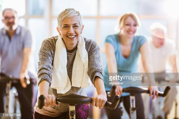 her age are not excuse for active lifestyle! - spinning stock pictures, royalty-free photos & images