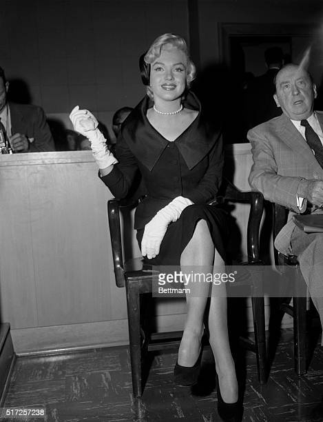 Her blonde hair highlighted by a somber black suit actress Marilyn Monroe smiles during her appearance in Santa Monica Superior Court to obtain a...