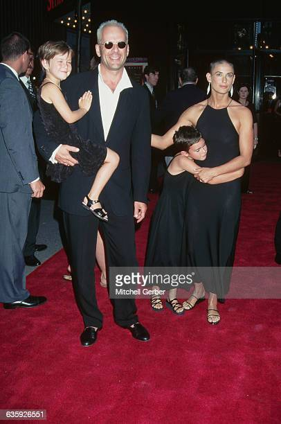 Her head still shaved from her role in GI Jane Demi Moore attends the premiere of Striptease with her family husband Bruce Willis holding daughter...