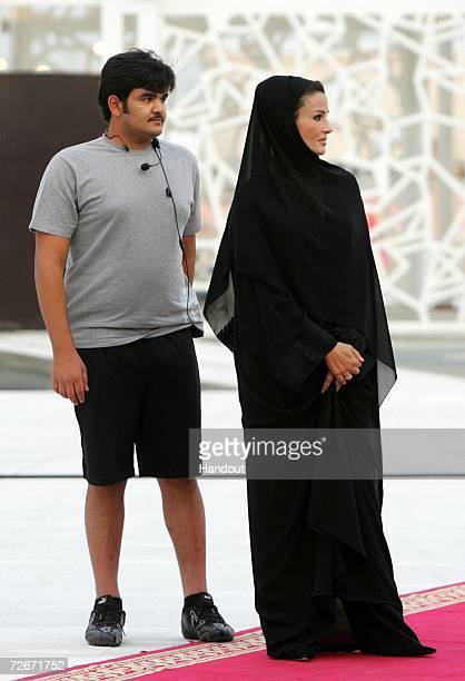 Her Highness Sheikha Mozah Bint Nasser Abdullah Al Missned Consort of the Emir of Qatar stands with her son Sheikh Hamad Bin Khalifa AlThani the...