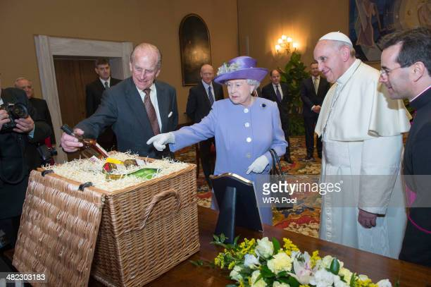 Her Majesty Queen Elizabeth II and Prince Philip Duke of Edinburgh exchange gifts with His Holiness Pope Francis during an audience in the Pope's...