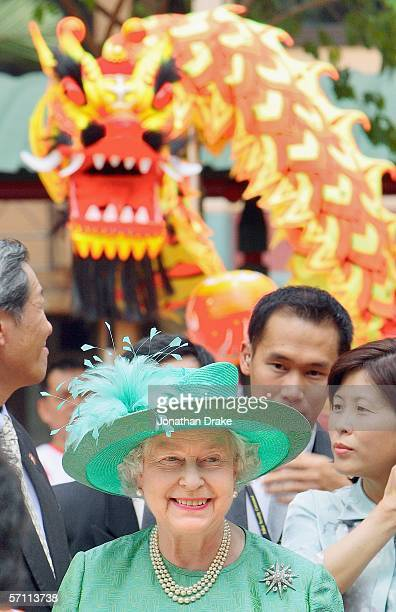 Her Majesty Queen Elizabeth II tours a housing estate while a dragon dance troupe hovers behind on March 17 2006 in Singapore Queen Elizabeth II seen...