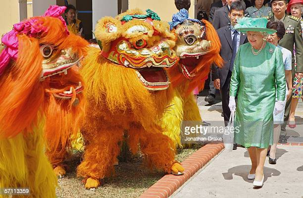 Her Majesty Queen Elizabeth II walks past a lion dance troupe during her tour of a housing estate in Singapore on March 17 2006 Queen Elizabeth II...