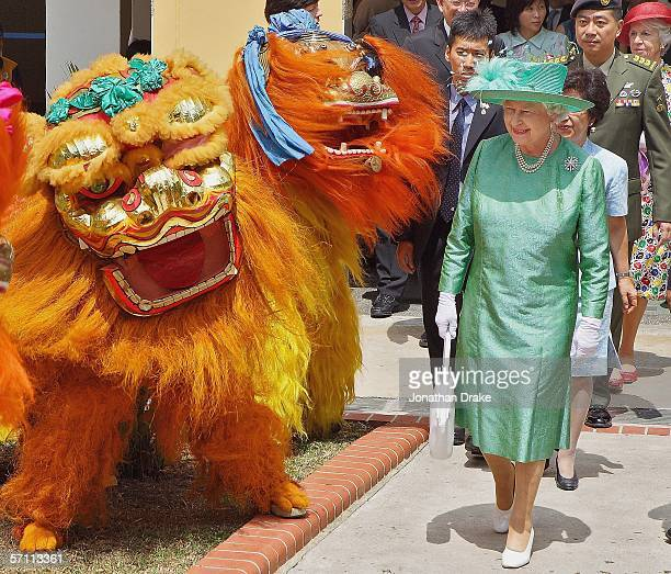 Her Majesty Queen Elizabeth II walks past a lion dance troupe while touring a housing estate in Singapore on March 17 2006 Queen Elizabeth II seen...