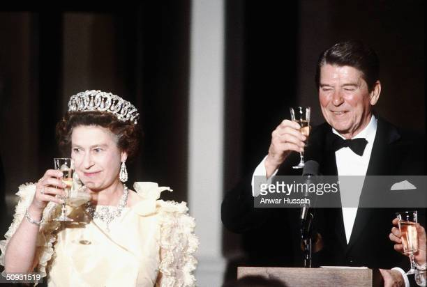 Her Majesty Queen Elizabeth II, wearing tiara and diamonds, makes a toast with former US President Ronald Reagan at a banquet in 1983, inSan...