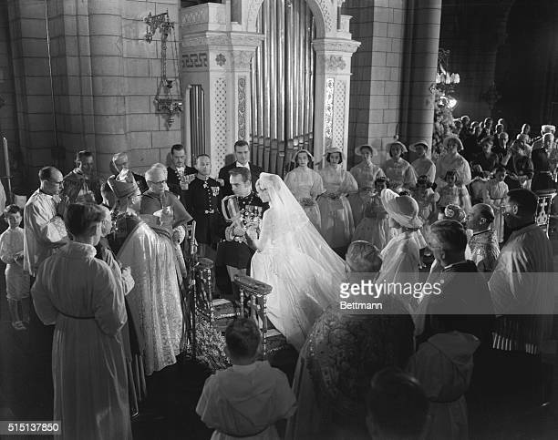 Her serene highness, Princess Grace Patricia, assists Prince Rainier III as he has some difficulty in putting the ring on her finger during colorful...