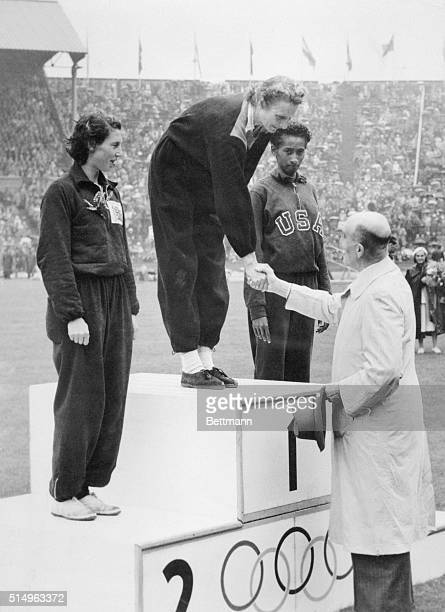 Her Third Gold Medal. London: Triple Olympic gold medallist, Mrs. Fanny Blankers-Koen receives her award from Colonel P.W. Scharroo on the victor's...