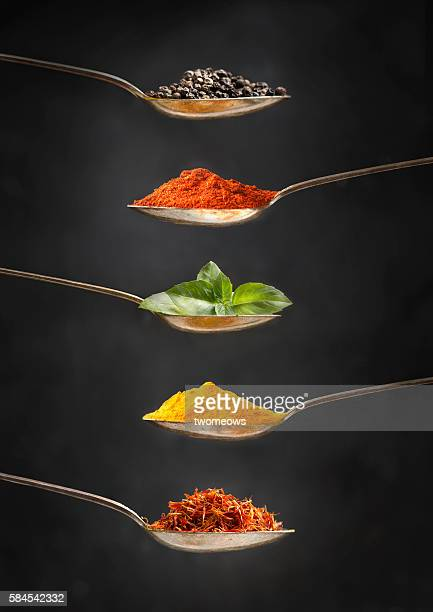 Herb and spices in silver spoon on rustic wooden background.