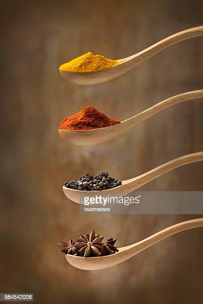 Herb and spices in wooden spoon on rustic wooden background.