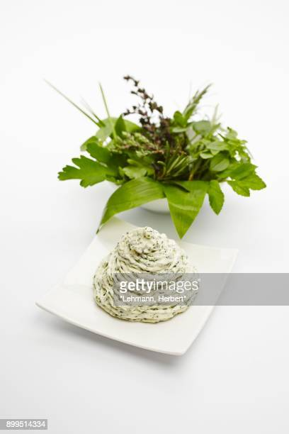 Herb butter next to a bowl of fresh herbs