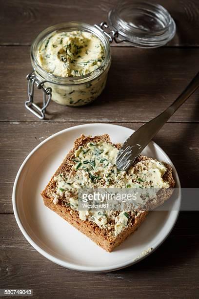 Herb butter, slice of spelt bread on plate
