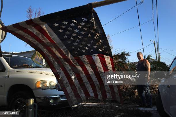 Herb Spencer cleans up around his home near an American flag covered with mud that he found near his home as people begin the process of rebuilding...