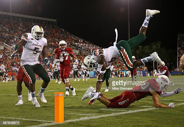 Herb Waters of the Miami Hurricanes jumps over Marcus Clark of the Florida Atlantic Owls during the a game at FAU Stadium on September 11 2015 in...