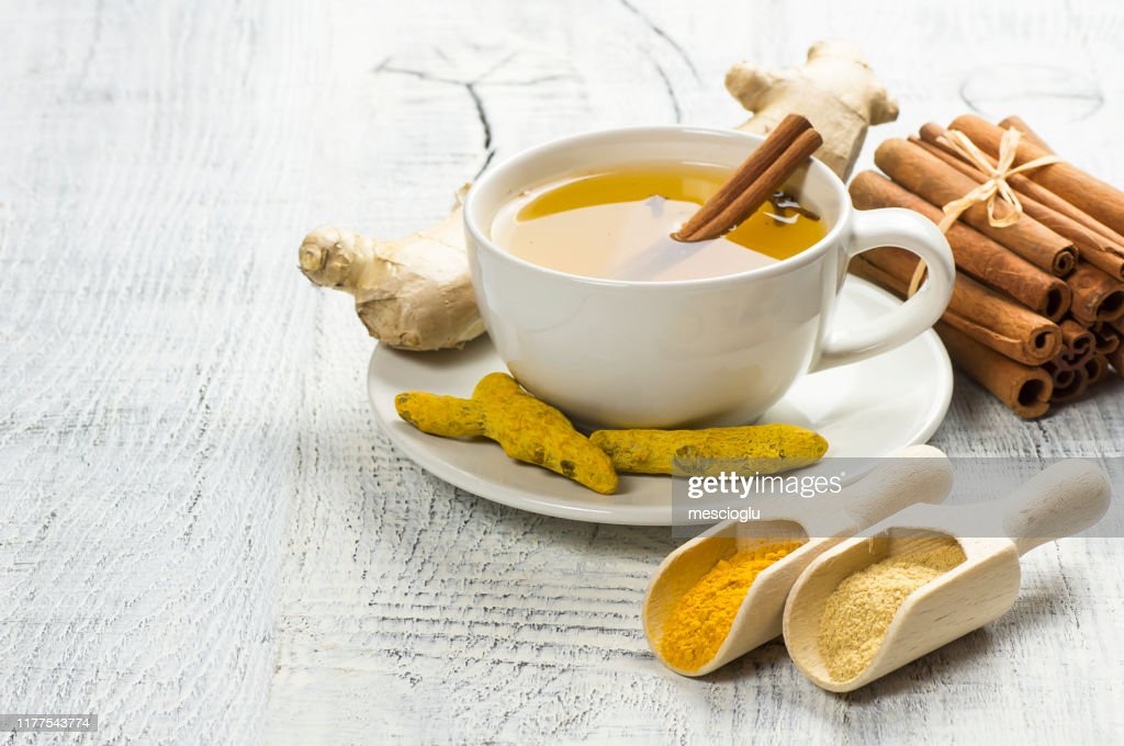 Herbal ginger and turmeric tea in white cup with ginger root, dry turmeric, cinnamon sticks and their powder : Stock Photo