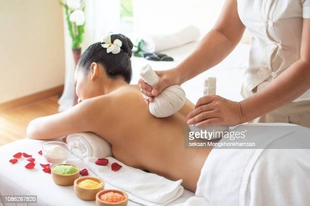 herbal massage in a spa - thai massage stockfoto's en -beelden