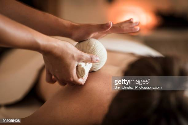 herbal massage in a spa - spa stock pictures, royalty-free photos & images