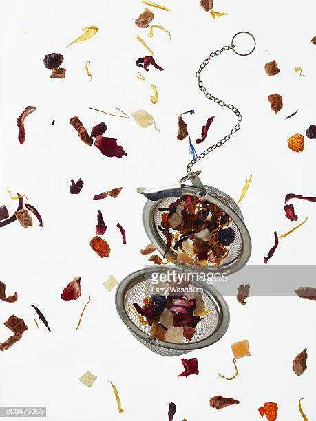 Herbal petals and tea strainer over white background