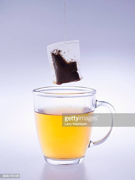 Herbal tea cup and teabag over blue background