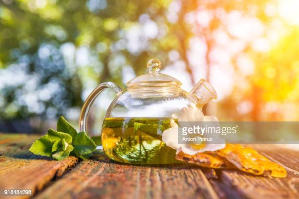 Herbal tea on a wooden table with biscuits and mint