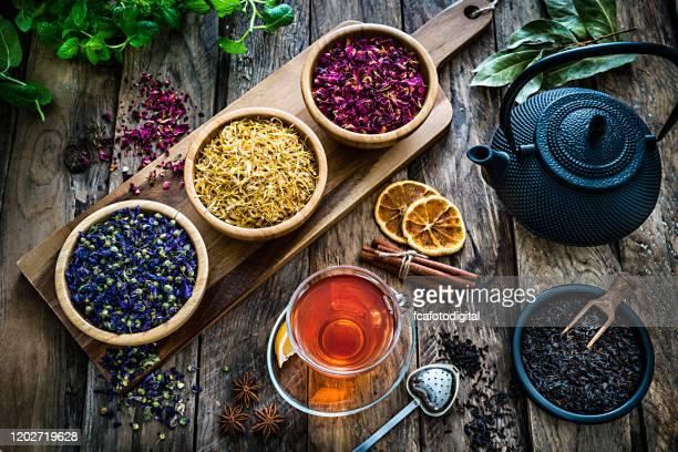 ハーブティー:様々な乾燥した茶葉と素朴な木製のテーブルの上から撮影された花とティーカップ - 温かいお茶 ストックフォトと画像