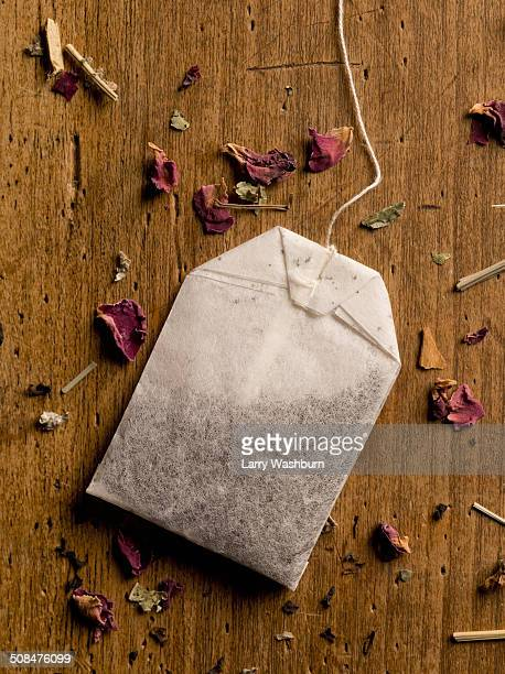 Herbal teabag and petals on wooden table