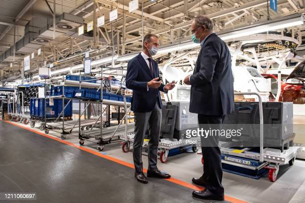 Herbert Diess , Chairman of the Board of Management of Volkswagen AG, and Stephan Weil , Prime Minister of Lower Saxony wear face masks during a...