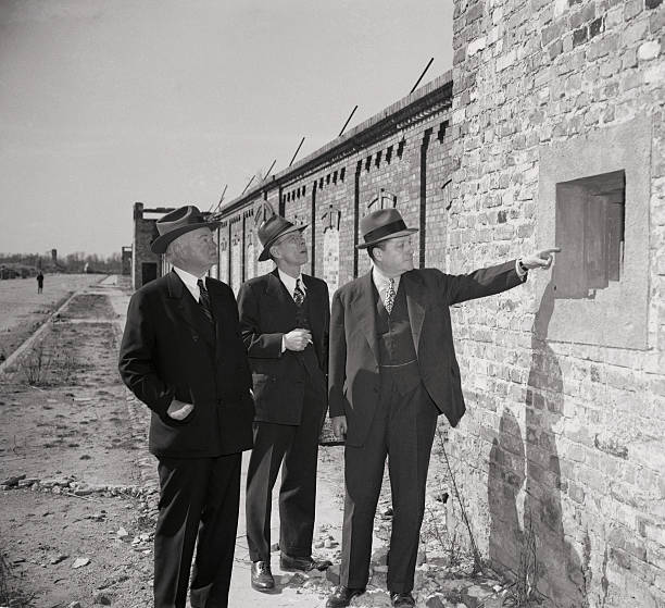 Herbert Hoover looks at a well protected gun slit in the Ghetto Wall of Warsaw From the safety of the slits Nazis would blast at defenseless Jews...