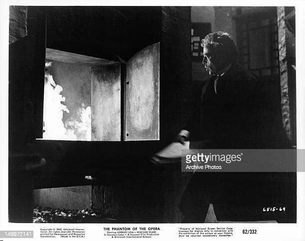 Herbert Lom throwing documents into fire in a scene from the film 'The Phantom Of The Opera' 1962