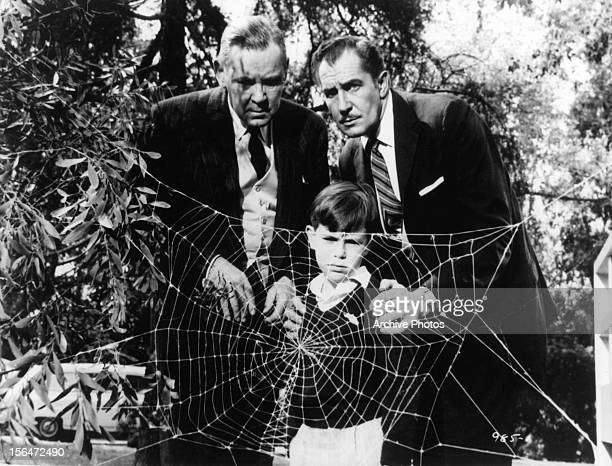 Herbert Marshall and Vincent Price holding boy as they watch spider about to devour fly in a scene from the film 'The Fly' 1958