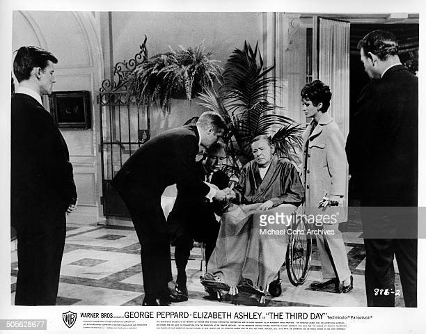 Herbert Marshall in a wheel chair tries to tap out a message for George Peppard as Roddy McDowall and Elizabeth Ashley look on in a scene from the...